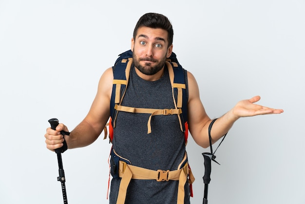 Homme jeune alpiniste avec un gros sac à dos et bâtons de randonnée isolé sur blanc ayant des doutes avec l'expression du visage confus