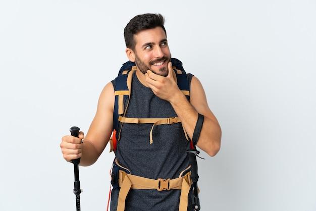 Homme jeune alpiniste avec un gros sac à dos et bâtons de randonnée isolé sur fond blanc en pensant à une idée