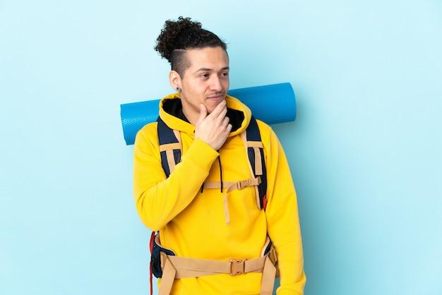 Homme jeune alpiniste avec un gros sac à dos sur fond bleu isolé pensant une idée