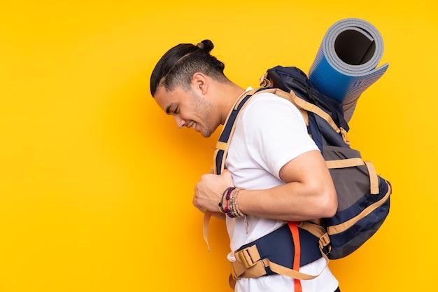 Homme jeune alpiniste avec un gros sac à dos sur fond isolé