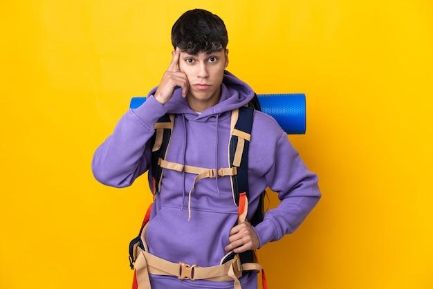 Homme jeune alpiniste avec un gros sac à dos sur fond jaune isolé pensant une idée