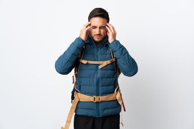 Homme jeune alpiniste avec un gros sac à dos isolé sur un mur blanc mécontent et frustré par quelque chose. expression faciale négative