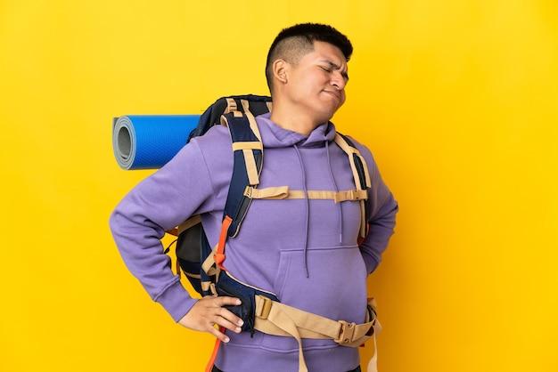 Homme jeune alpiniste avec un gros sac à dos isolé