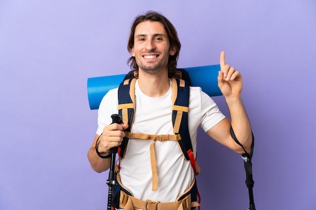 Homme jeune alpiniste avec un gros sac à dos pointant vers le haut une excellente idée