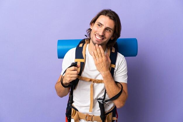 Homme jeune alpiniste avec un gros sac à dos regardant en souriant