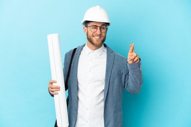 Homme jeune architecte avec casque et tenant des plans avec les doigts qui se croisent et souhaitant le meilleur