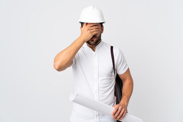 Homme jeune architecte avec casque et tenant des plans isolés sur blanc couvrant les yeux par les mains