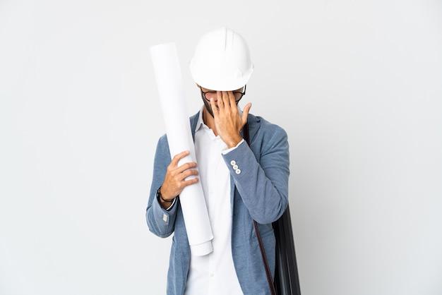 Homme jeune architecte avec casque et tenant des plans isolés sur un mur blanc avec une expression fatiguée et malade