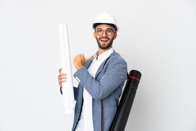 Homme jeune architecte avec casque et tenant des plans isolés