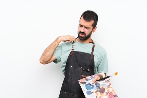 Homme jeune artiste tenant une palette sur un mur isolé avec expression fatiguée et malade