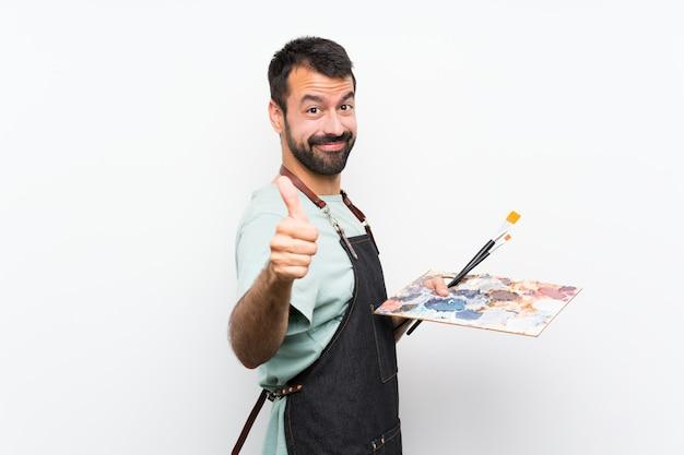 Homme jeune artiste tenant une palette sur un mur isolé avec le pouce levé parce que quelque chose de bien s'est passé