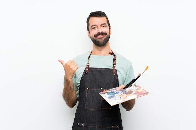 Homme jeune artiste tenant une palette sur un mur isolé avec les pouces vers le haut de geste et souriant