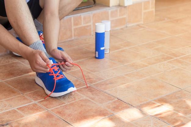 Homme jeune athlète asiatique attachant des chaussures de course dans la maison avant, coureur masculin prêt pour le jogging
