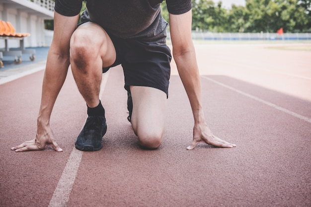 Homme jeune athlète fitness prépare à courir sur la piste, concept de bien-être entraînement