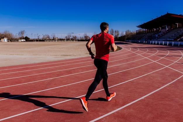 Homme jeune athlète qui court dans les ruelles. lumière du jour. concept sportif