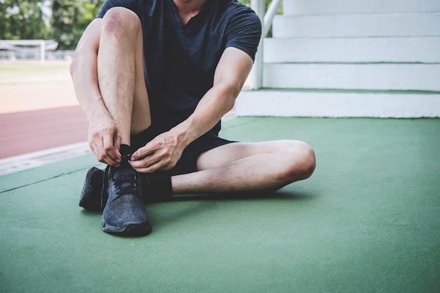 Homme jeune athlète de remise en forme en cours d'exécution sur piste, exercice de bien-être et coureur attachant des lacets avec espace de copie avant la course