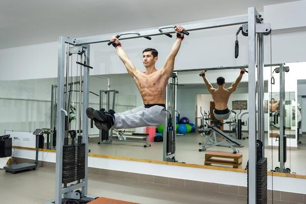 Homme jeune et athlétique, faire des exercices sur la barre transversale