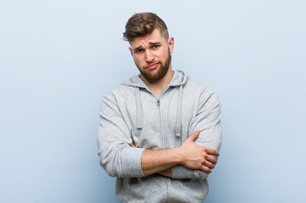 Homme jeune beau fitness mécontent de l'expression sarcastique.