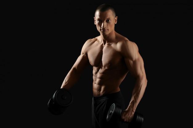 Homme jeune bodybuilder posant avec des haltères souriant posant torse nu avec son torse en forme et tonique