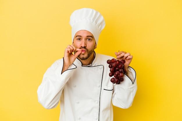 Homme jeune chef caucasien tenant des raisins isolés sur un mur jaune avec les doigts sur les lèvres en gardant un secret.