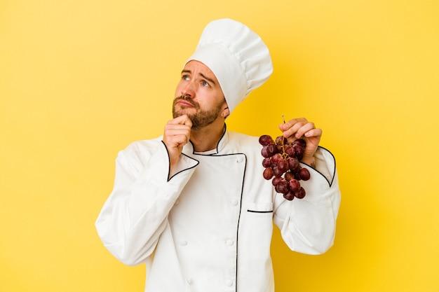Homme jeune chef caucasien tenant des raisins isolés sur un mur jaune à la recherche de côté avec une expression douteuse et sceptique.
