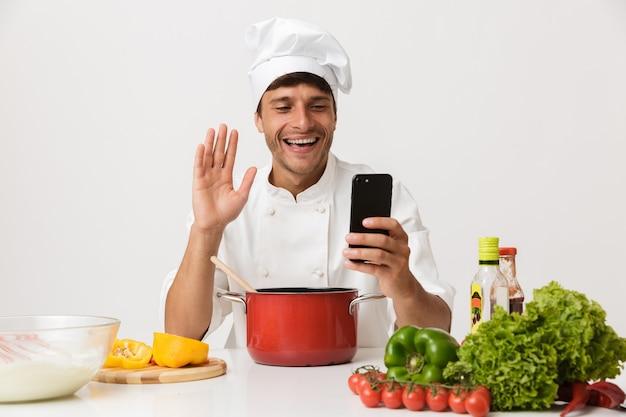 Homme jeune chef isolé sur mur blanc cuisson à l'aide d'un téléphone mobile en agitant.