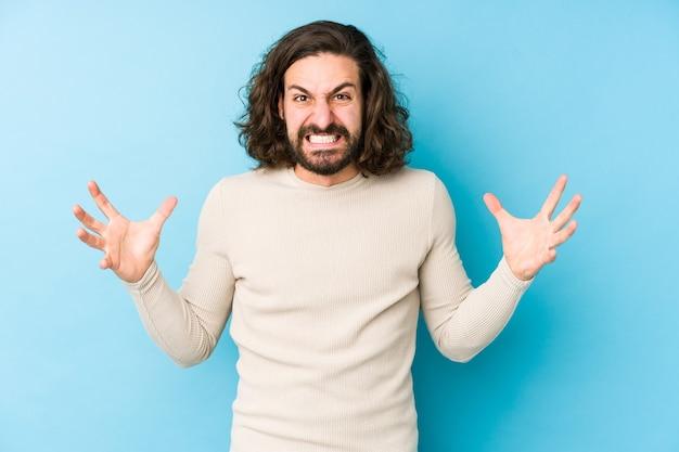 Homme jeune cheveux longs isolé sur un mur bleu criant de rage.