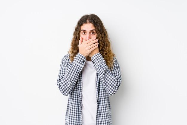Homme jeune cheveux longs posant isolé choqué couvrant la bouche avec les mains.