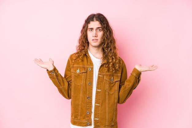 Homme jeune cheveux longs posant isolé confus et douteux en haussant les épaules pour tenir un espace de copie.