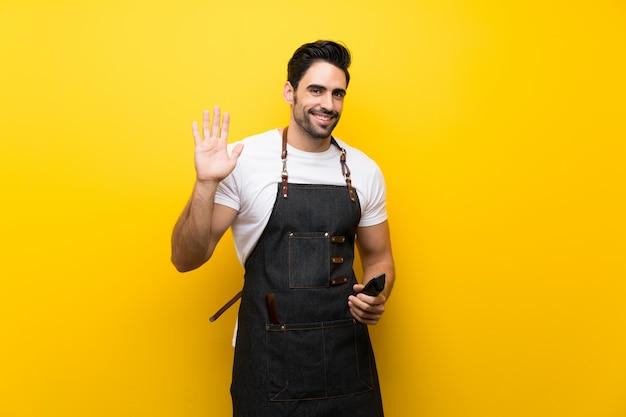 Homme jeune coiffeur saluant avec la main avec une expression heureuse