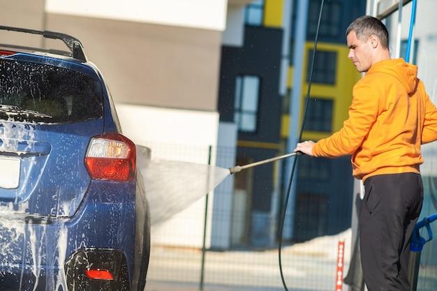 Homme jeune conducteur lavant sa voiture avec un jet d'eau haute pression sans contact dans un lave-auto en libre-service.