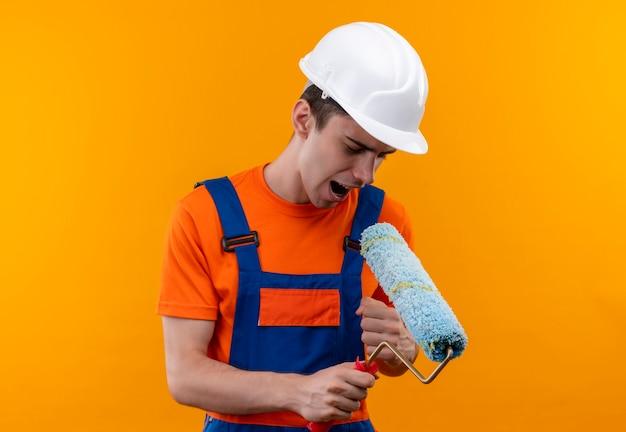 Homme jeune constructeur portant l'uniforme de construction et un casque de sécurité chantant dans une brosse à rouleau
