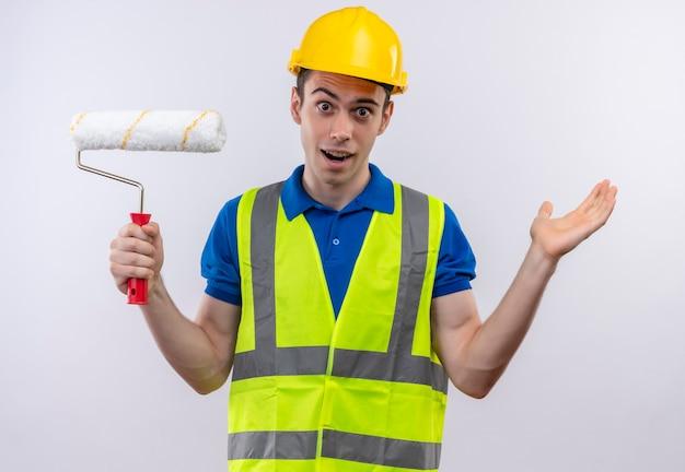 Homme jeune constructeur portant l'uniforme de construction et un casque de sécurité surpris tient une brosse à rouleau blanc
