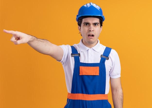 Homme jeune constructeur en uniforme de construction et casque de sécurité à l'avant confus et inquiet en pointant avec l'index quelque chose debout sur le mur orange
