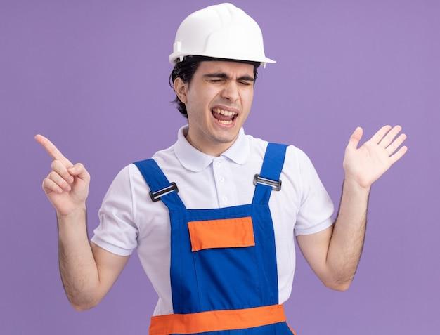 Homme jeune constructeur en uniforme de construction et casque de sécurité heureux et joyeux pointant avec l'index sur le côté debout sur le mur violet