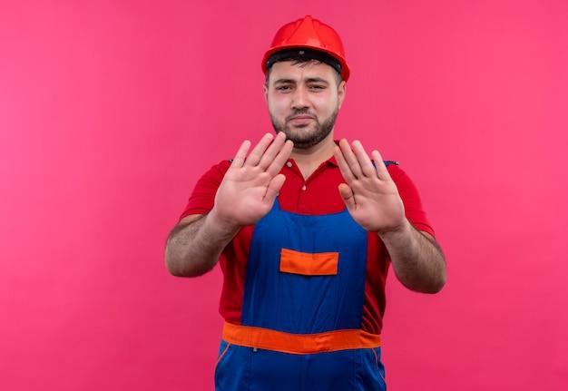 Homme jeune constructeur en uniforme de construction et casque de sécurité avec les mains ouvertes faisant panneau d'arrêt