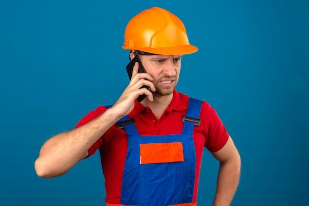 Homme jeune constructeur en uniforme de construction et casque de sécurité parlant sur téléphone mobile malheureux dans le stress sur mur isolé bleu