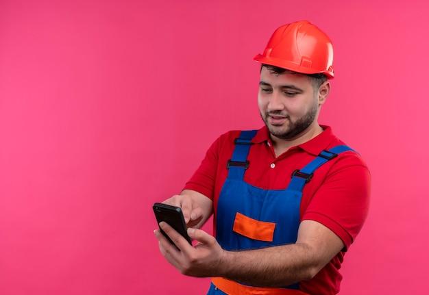 Homme jeune constructeur en uniforme de construction et casque de sécurité tenant un téléphone mobile à la recherche de plaisir et positif