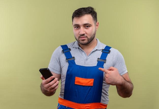 Homme jeune constructeur en uniforme de construction holding smartphone pointant avec le doigt à la confiance