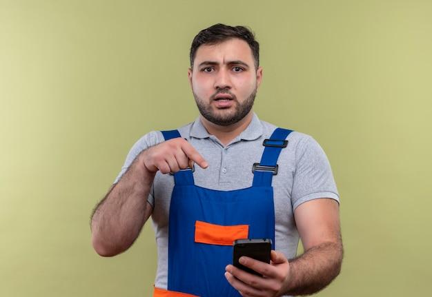 Homme jeune constructeur en uniforme de construction holding smartphone pointant avec le doigt à la recherche confus