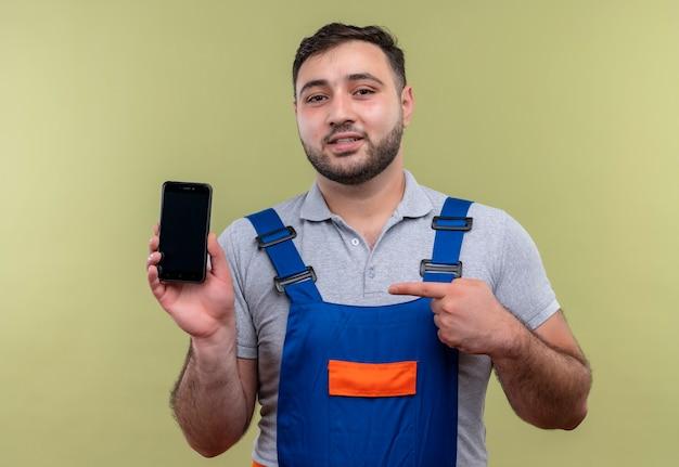 Homme jeune constructeur en uniforme de construction montrant smartphone pointant avec le doigt à la confiance