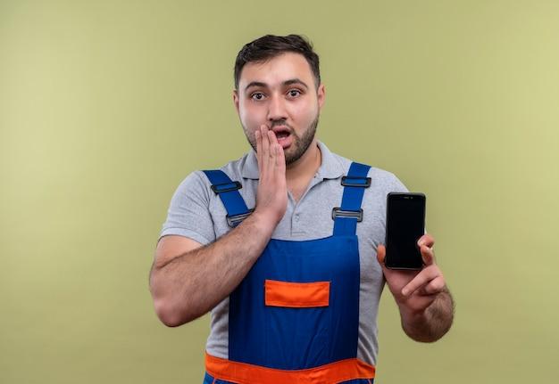 Homme jeune constructeur en uniforme de construction montrant le smartphone à la surprise et la surprise