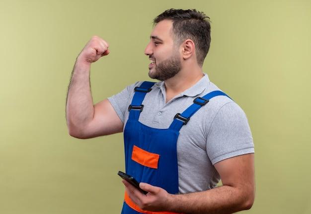 Homme jeune constructeur en uniforme de construction tenant le poing serrant le smartphone heureux et sorti se réjouissant de son succès