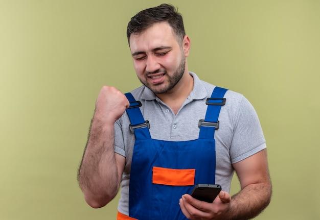 Homme jeune constructeur en uniforme de construction tenant le poing serrant le smartphone heureux et sorti