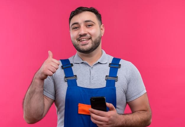 Homme jeune constructeur en uniforme de construction tenant un smartphone montrant les pouces vers le haut en souriant