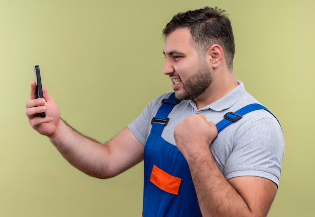 Homme jeune constructeur en uniforme de construction tenant un smartphone à la recherche d'éboulis posant comme gagnant poing serrant heureux et sorti