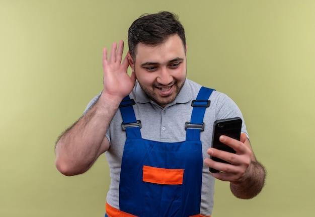 Homme jeune constructeur en uniforme de construction tenant le smartphone tenant la main près de l'oreille en essayant d'écouter