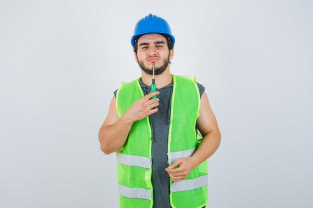 Homme jeune constructeur en uniforme tenant la pointe du tournevis sur le menton et à la vue réfléchie, de face.