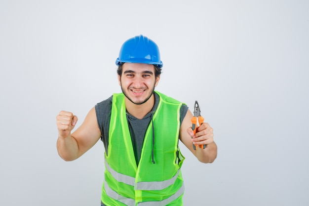 Homme jeune constructeur en uniforme de vêtements de travail tenant des pinces tout en montrant le geste du gagnant et à la chance, vue de face.