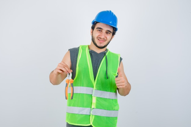 Homme jeune constructeur en uniforme de vêtements de travail tenant des pinces tout en montrant le pouce vers le haut et à la vue de face, heureux.